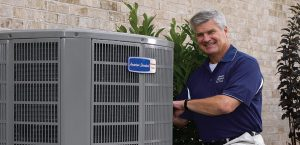 Service technician fixing an air conditioner outside a customers home.