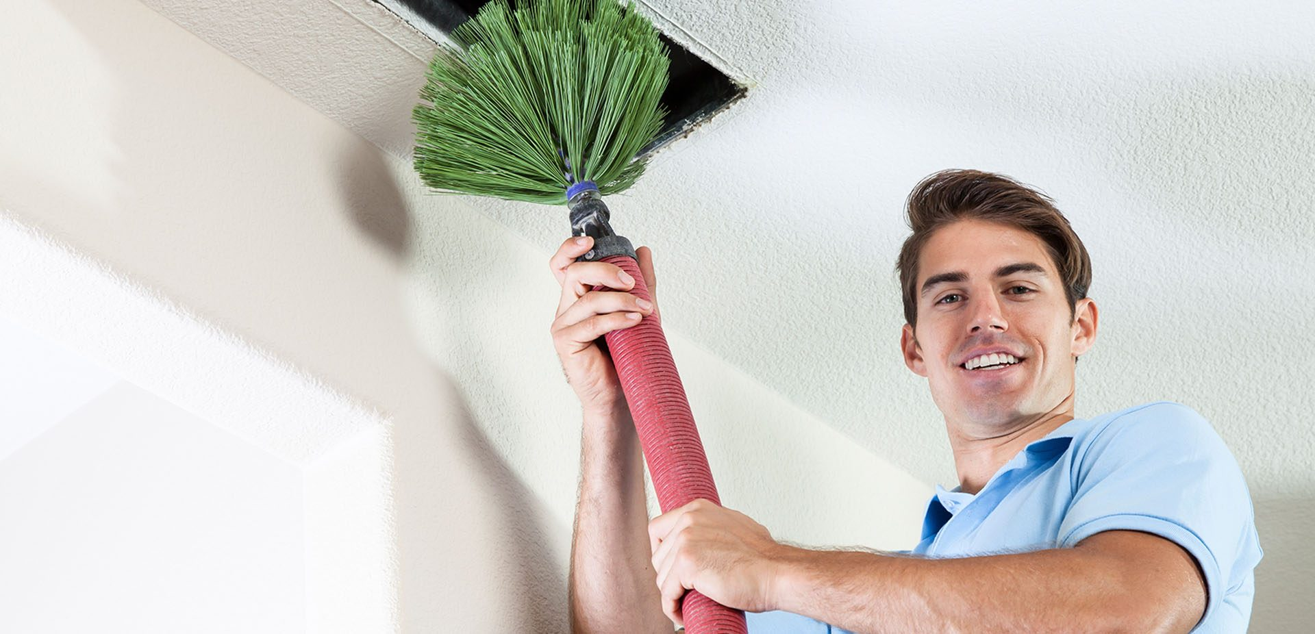 Indoor air quality specialist cleaning air ducts with HVAC duct cleaning machine